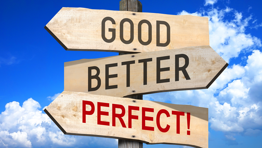 On old fashioned wooden sign with 3 arrows pointing in different directions. The three arrows read, 'Good, Better, Perfect!' the background is a stark blue sky with puffy white clouds.