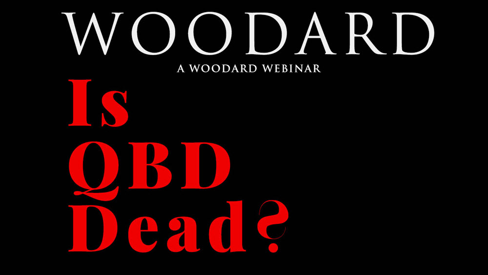 A very dark graphic - in face the background is only black. Top third of the horizontal image is the word 'woodard' in white thin text with the lower 2 thrids in large thick red font says 'is QBD dead?'